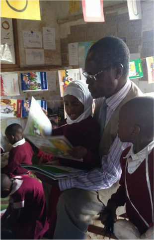 Commissioner for Education Dr. Edicone Shirima (Pictured reading books with pre-primary students at Mwenge School
