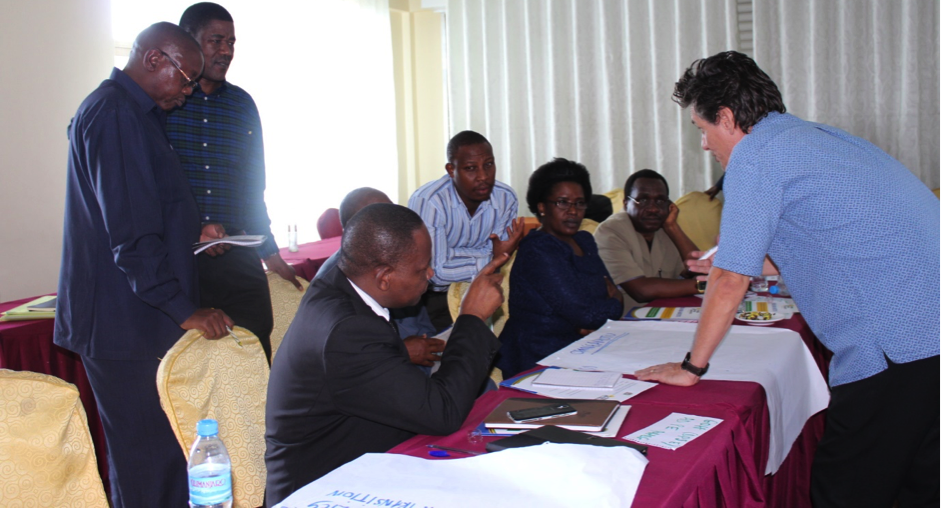 Benjamin Oganga (seated left) elaborating a point to Craig Ferla (standing right) during a group discussion.