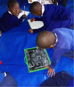 Mwenge Primary School students enjoying a pre-writing session in a classroom that has ample space.