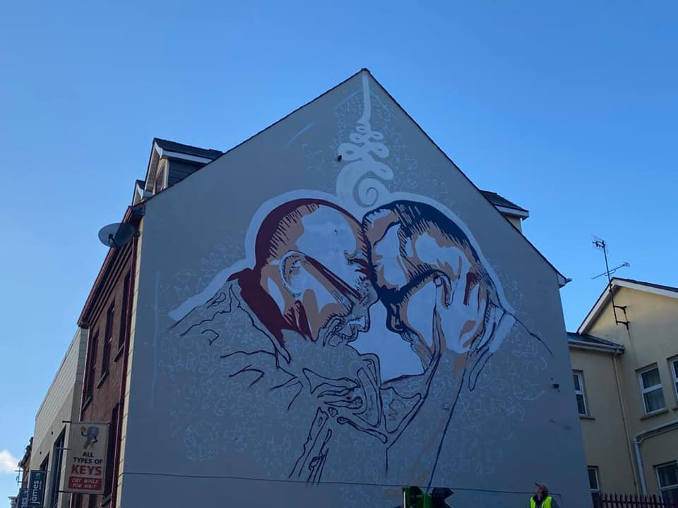 Mural on wall in derry showing the Daiai Lama and Richard Moore
